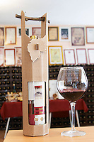 A bottle of Zlatna in a curious box with a vine twig handle and a glass of wine. , in the winery tasting room. Vukoje winery, Trebinje. Republika Srpska. Bosnia Herzegovina, Europe.