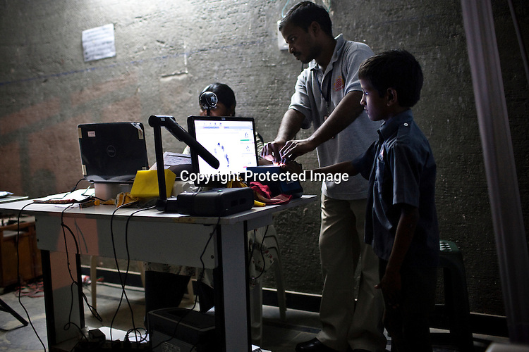 An official assists a young boy while he places his fingers for fingerprint scan during the enrollment process in Naagaaram village, outskirts of Hyderabad in Andhra Pradesh, India. India is assigning each one of its 1.2 billion people a unique ID number based on digital finger prints and iris scan. Photograph: Sanjit Das/Panos