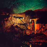 Twin turret mobile drilling machine working in underground copper mine..