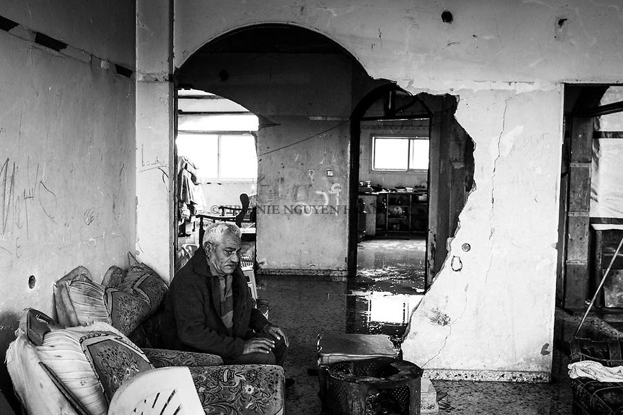 Gaza, Beit Hanoun: Abdelraman Abu Ouda est assis dans son salon d&eacute;truit par les bombardements israeliens de l&rsquo;&eacute;t&eacute; 2014. Lorsqu&rsquo;il pleut, l&rsquo;eau passe &agrave; travers les murs et innonde le sol de la maison. 24/01/16 <br /> <br /> Gaza, Beit Hanoun: Abdelraman Abu Ouda is sitting in his living room destroyed by Israeli bombing in the summer of 2014. When it rains , the water passes through walls and inundates the floor of the house. 24/01/16