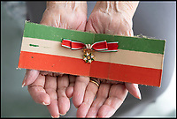 BNPS.co.uk (01202 558833)Pic:  PhilYeomans/BNPS<br /> <br /> Gabriella with her Star of Italy and a Italian Partisans armband.<br /> <br /> Brighton nonagenarian Gabriella Ezra(91) has finally been recognised for her wartime heroics...<br /> <br /> The extraordinary story of how a teenage girl saved an entire village from being executed by the Nazis has come to light after she finally received a gallantry award nearly 74 years later.<br /> <br /> Fearless Gabriella Ezra, 91, who lives in Brighton, Sussex, intervened to stop her father Luigi and 37 other inhabitants of a rural village in her native Italy from being massacred by a firing squad during the chaotic last days of WW2.<br /> <br /> She has now been awarded an Italian Star of Italy medal after her son Mark wrote to the Italian embassy to make them aware of her remarkable actions on the morning April 28, 1945.<br /> <br /> Gabriella, who was 17 years old at the time, chased after a German officer and pleaded with him to show mercy to the villagers of Capella di Scorze, near Venice, who had been rounded up and locked in a cowshed.<br /> <br /> The Germans were after retribution following an attack on their men by Italian partisans which had left several of them wounded.