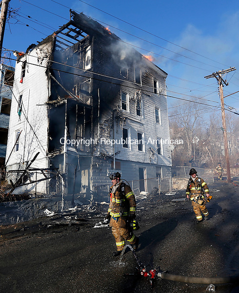 Waterbury, CT- 11 April 2015-041115CM18-   Waterbury firefighters take a moment while fighting a fire on Orange Street in Waterbury on Saturday.  An afternoon fire destroyed a multifamily house.   Christopher Massa Republican-American