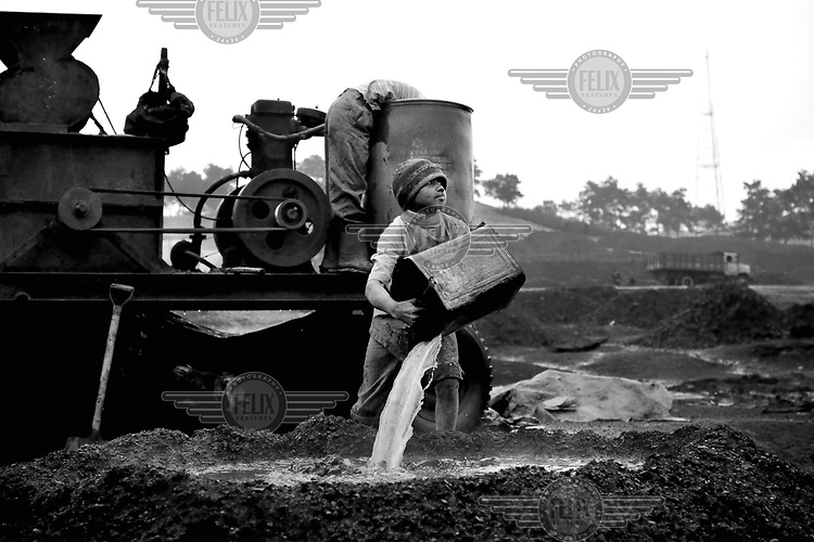 A boy pours water into a pile of coal at the Kong Ong Depot, the largest coal storage depot in the Jaintia Hills. The coal comes from privately owned mines in the surrounding region. There are approximately 5,000 privately owned coal mines in the region sitting on top of about 40 million tons of coal. Many use children, often trafficked, to work them under conditions that are hard and unregulated. The coal is dug out using primitive methods and basic tools.