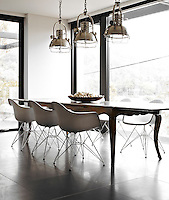 The dining area is furnished with an antique French table surrounded by a set of Eames chairs