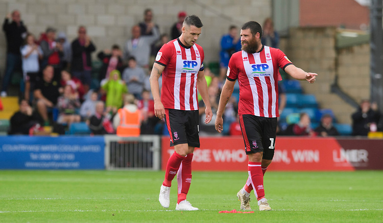 Lincoln City's Jason Shackell, left, and Lincoln City's Michael Bostwick<br /> <br /> Photographer Chris Vaughan/CameraSport<br /> <br /> The EFL Sky Bet League One - Lincoln City v Fleetwood Town - Saturday 31st August 2019 - Sincil Bank - Lincoln<br /> <br /> World Copyright © 2019 CameraSport. All rights reserved. 43 Linden Ave. Countesthorpe. Leicester. England. LE8 5PG - Tel: +44 (0) 116 277 4147 - admin@camerasport.com - www.camerasport.com