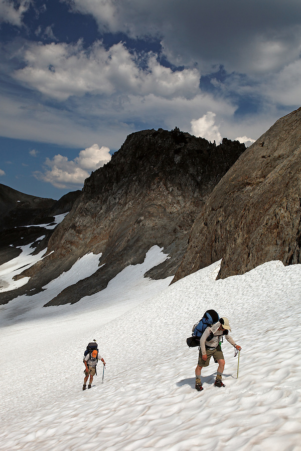 Backpackers climbing snow slope, Bailey Range Traverse, Olympic Mountains, Washington