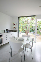 The silver-and-white kitchen opens out to a view of old cherry trees framed by the stainless steel of the floor-to-ceiling window