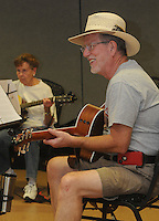 NWA Democrat-Gazette/FLIP PUTTHOFF<br /> FINGERS AT WORK<br /> Guitar teacher Mike Haley leads lessons Tuesday August 18 2015 at the Adult Wellness Center in Rogers. Student Pat Calnan (left) follows along. About a dozen students are enrolled in guitar lessons at the center. A picking circle is held at 1 p.m. each Tuesday for any guitar players who wish to play and sing.