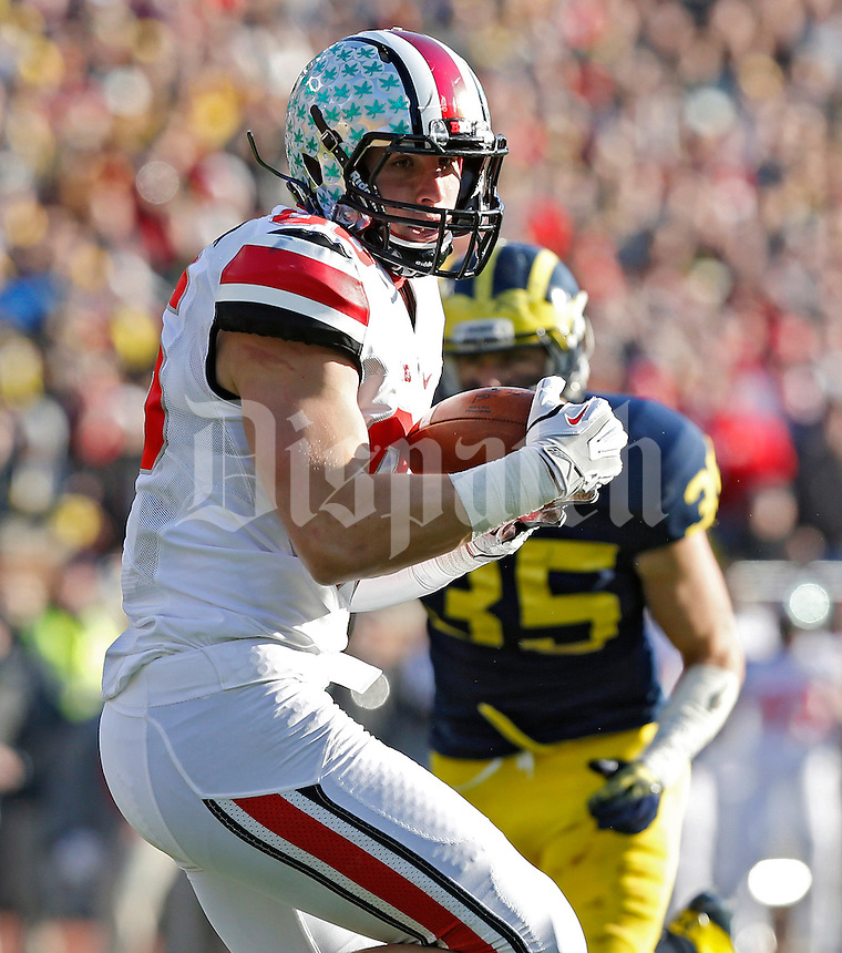 Ohio State Buckeyes tight end Jeff Heuerman (86) makes a catch and then scores a touchdown against Michigan Wolverines defense in the 3rd quarter of their college football game at Michigan Stadium in Ann Arbor, Michigan on November 30, 2013.  (Dispatch photo by Kyle Robertson)