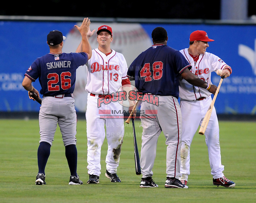 Members of the Rome Braves, including Will Skinner (26), left, and William Beckwith (48), second from right, and Greenville Drive, including Nate Striz (13) and Matt Marquis (23), celebrate the end of a mock battle, attacking from opposite sides of the field, during a lengthy rain delay before a game on July 5, 2012, at Fluor Field at the West End in Greenville, South Carolina. (Tom Priddy/Four Seam Images)