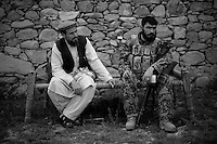 An Afghan National Army platoon leader sits at a meeting with a village elder during a routine patrol in Northern Kunar Province, Afghanistan on Thursday March 25 2010..The Afghan soldier is  from 1st Coi ( Company ), 1st Kandak ( battalion ) 2nd Brigade.