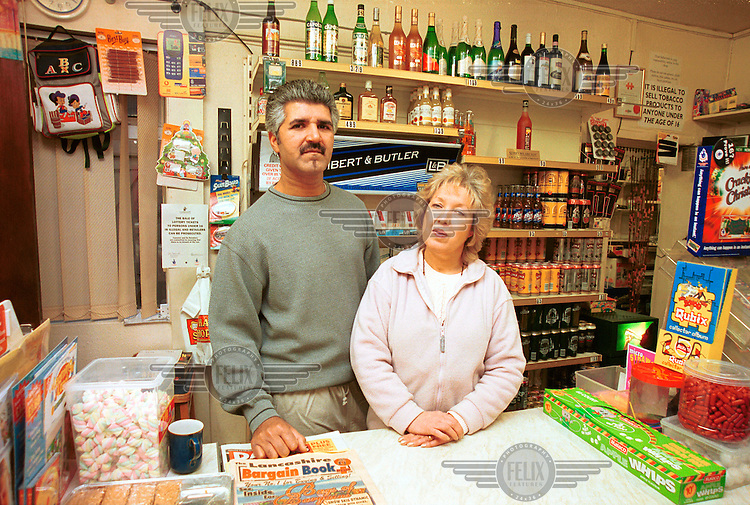 British Asian shopkeeper Mal Hussein, who has been a victim of racist attacks, stands at the counter of his shop with his partner, Linda, on Ryelands Housing Estate.