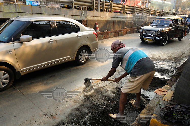 Cars passing a labourer doing road work.