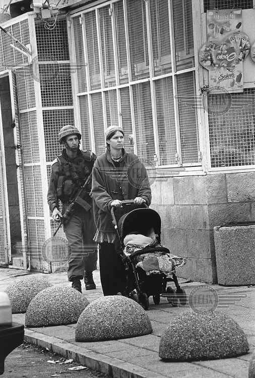 An Israeli soldier shadows a settler pushing a pram as she leaves a heavily-fortified Israeli store in central Hebron.