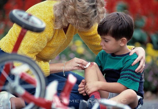 Mother tending a son's scraped knee having fallen off a tricycle