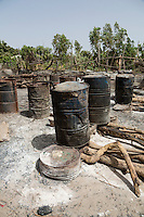 Distillery, where Cashew Apple Juice is Converted into Alcohol. After being heated in barrels resting on firewood, the vapor travels in metal tubes through barrels containing water to cool and condense the alcohol enroute to its collection point.    The Gambia.