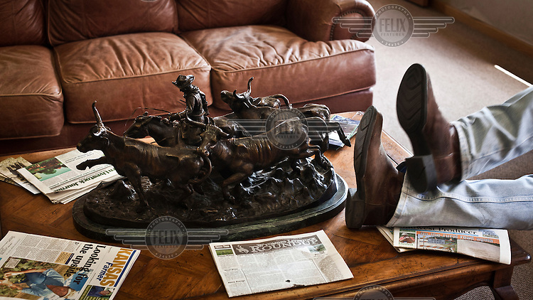 A man puts his feet up at an auction house in Dodge City, Kansas. The centrepiece of the table he rests on is a bronze statue of a cowboy herding beef cattle. Around the ornament are scattered various farming industry newspapers..