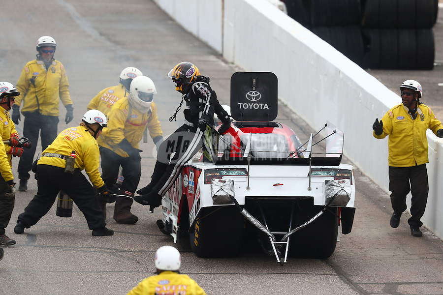 Feb 26, 2017; Chandler, AZ, USA; The safety safari tends to NHRA funny car driver Del Worsham after an engine fire during the Arizona Nationals at Wild Horse Pass Motorsports Park. Mandatory Credit: Mark J. Rebilas-USA TODAY Sports