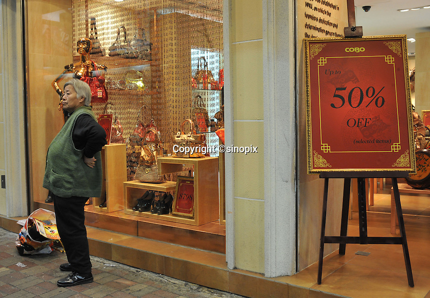 A clothes store offers 50% off in a sale in Hong Kong's Central district. Hong Kong's slumping economy will shrink further in the first half of 2009..