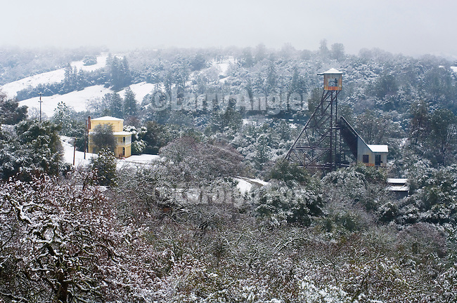 Historic Kennedy Mine House and headframe covered  snow in the Sierra Nevada Foothills of Amador County, Calif.
