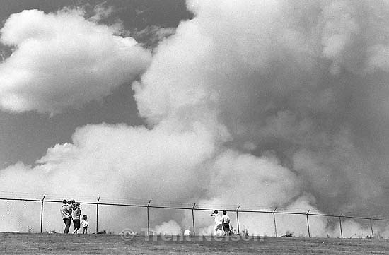 People watch a fire at the dump.<br />