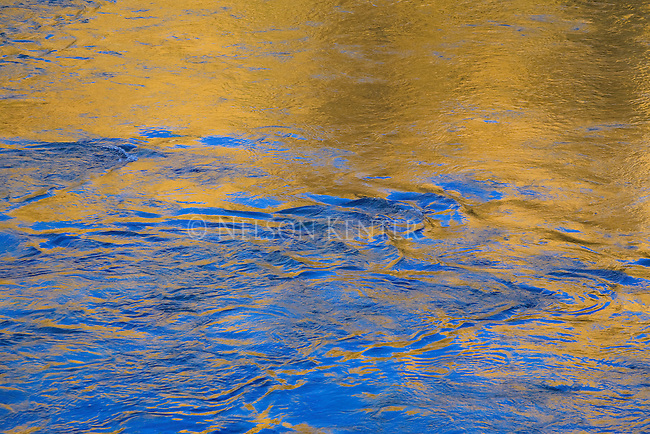 Rippling water and light reflection creates patterns and shapes on the surface of a river