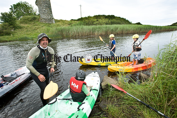 David Ryan of Doonbeg Ocean Evolution  helping local children into  the river during the kayak trials held as part of the Doonbeg Seafood Festival. Photograph by John Kelly,