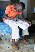 CAPE TOWN, SOUTH AFRICA - MARCH 15: Sikhumbuzo Hlahleni, age 15, a student at Cape Town City Ballet's youth company does his geography homework in his family house on March 15, 2010 in Khayelitsha, South Africa. He trains in Cape Town every Saturday. He also trains a few days week at home in Khayelitsha, a poor township outside Cape Town. He has to change taxi three times to get to the school. (Photo by Per-Anders Pettersson).