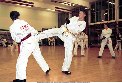 Boys practice their TAEKWONDO moves, Taekwondo Class, The Grange School, Aylesbury, 000214. Photo: Neil Tingle/Action Plus....2000.martial art.arts.combat sport.sports.lesson.child.children.kids.boy.boys.youth.youths.teenager.teenagers.Youngster.Youngsters.childrens sport.children's sport.indoor hall.T'aekwondo tae kwondo tae kwon do