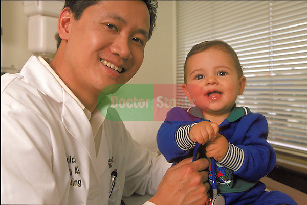 portrait of smiling male doctor holding infant with sthethoscope