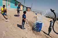 A Peruvian water distribution worker with a pipe splashes drinking water from a truck into a plastic barrel on the dusty hillside of Pachacútec, a desert suburb of Lima, Peru, 20 January 2015. Although Latin America (as a whole) is blessed with an abundance of fresh water, having 20% of global water resources in the the Amazon Basin and the highest annual rainfall of any region in the world, an estimated 50-70 million Latin Americans (one-tenth of the continent's population) lack access to safe water and 100 million people have no access to any safe sanitation. Complicated geographical conditions (mainly on the Pacific coast), unregulated industrialization (causing environmental pollution) and massive urban poverty, combined with deep social inequality, have caused a severe water supply shortage in many Latin American regions.