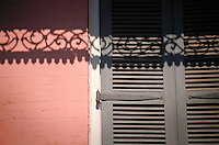 Shadow of wrought iron on colorful shutter. New Orleans Louisiana United States French Quarter.