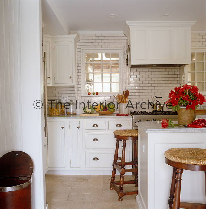 The gleaming white kitchen is the previous owner's renovation with walls clad in subway tiles from Ann Sacks