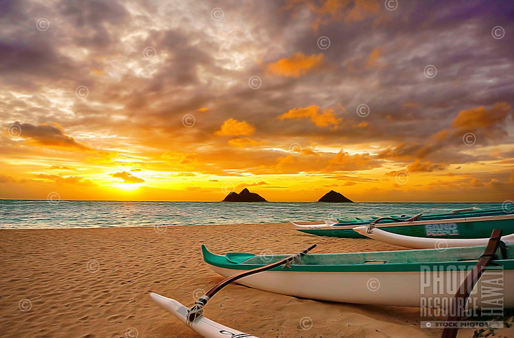 A stunning sunrise over the Mokulua Islands lights up outrigger canoes and Lanikai Beach, Windward O'ahu.