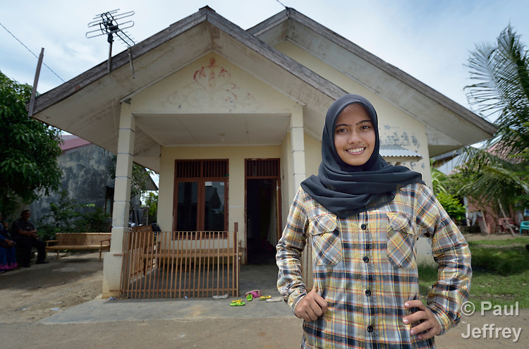 Nurul Aina stands in front of a home she owns in the Lam Pulo neighborhood of Banda Aceh, Indonesia. She was just 8 years old in 2004 when a massive tsunami swept over the city, killing her parents and two siblings and leveling their home. Aina was fortunately visiting relatives in a neighborhood far from the seashore when the tsunami hit. With assistance from the Katahati Institute and Diakonie Katastrophenhilfe, a new house was built and titled in Aina's name, an accomplishment that required considerable legal advocacy by Katahati staff. As a result, rental income from the house has paid for Aina's schooling while she lives with her grandmother. Now 18, Aina is studying English at a local university, and plans to move into her house some day. The tsunami killed 221,000 people in Aceh province and left more than 500,000 displaced.