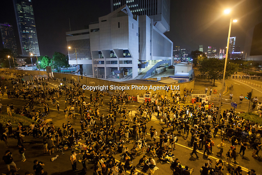 Occupy Central pro-democracy protesters are seen massing outside the Chinese People's Liberation Army (PLA) headquarters in Hong Kong, on the second day of the mass civil disobedience campaign Occupy Central, Central District, Hong Kong, China, 30 September 2014. The movement is also being dubbed the 'umbrella revolution' after the versatile umbrellas used to shield protesters from rain, sun - and police pepper spray.