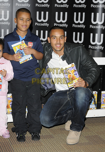 THEO WALCOTT & fan.Footballer Theo Walcott attending his booksigning session at Waterstone's Piccadilly, London, England, UK, November 4th 2010..book signing  full length black jacket leather jeans white t-shirt child kid boy Arsenal top shirt kneeling down grey gray .CAP/CAN.©Can Nguyen/Capital Pictures.