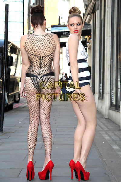 JPG Models.JPG & Diet Coke - photocall at Harvey Nichols, Knightsbridge, London, England..Two models pose for photos as award-winning body artist Carolyn Roper paints them as Diet Coke bottles, recreating Jean Paul Gaultier's latest 'Night & Day' designs for the brand..April 16th, 2012.full length posing black naked nude skin back behind rear hair up white striped stripes shoes fishnet red  .CAP/JEZ  .©Jez/Capital Pictures.