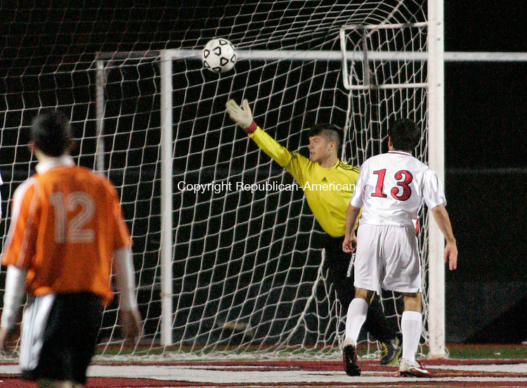 SOUTHBURY, CT 15 OCTOBER 2011--101711JS12---- Pomperaug's Mark Almeida (13) chips in a goal just past Watertown's David Hughes in the first half of their game Monday at Pomperaug High School in Southbury. <br /> Jim Shannon Republican-American