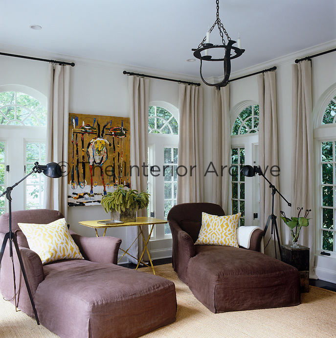 In the sun room, stone-brown slipcovered chaises are backlit by rows of windows dressed in Belgian linen curtains
