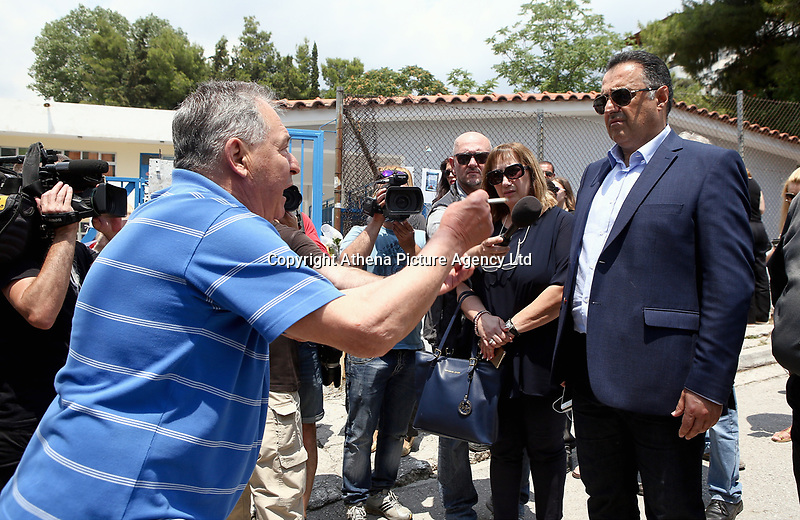 "Pictured: Local mayor Yiannis Kassavos (R) is shouted at by an irate man as he arrives at the 6th primary School in Acharnes, Athens, Greece. Saturday 10 June 2017<br /> Re: An 11 year old boy has been shot dead by a ""stray bullet"" during a school celebration in Acharnes (Menidi) area, in the outskirts of Athens, Greece.<br /> Marios Dimitrios Souloukos ""complained to his mum"" who works as a teacher at the 6th Primary School of Acharnes that he was feeling unwell, he then collapsed with blood pouring out from the top of his head.<br /> His mum tried to revive him assisted by other teachers while his schoolmates who were reportedly upset, were hurriedly removed by their parents.<br /> According to locals an ambulance arrived 25 minutes late.<br /> Hundreds of police officers have been deployed in the area and have raided many properties.<br /> Shells matching the fatal bullet which hit the boy on the top of his head were found in a house yard nearby.<br /> Local people reported hearing shots being fired at a nearby Romany Gypsy camp before the fatal incident.<br /> The area has been plagued with criminality during the last few years."