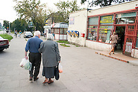 A couple of spry shoppers walking down Lutomierska Street Balucki District Lodz Central Poland