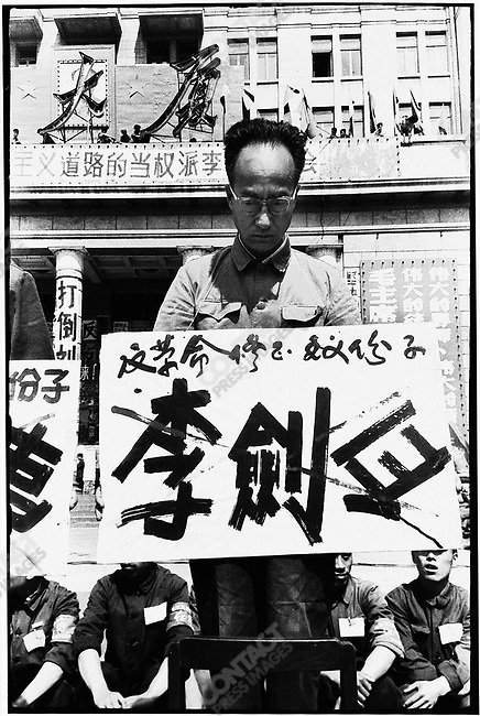 "Forced to stand on chairs in front of the North Plaza Hotel, the seven secretaries of the Heilongjiang Party committee are denounced for ""carrying out Liu Shaoqi's revisionist line."" Each wears a placard with his name crossed out and a description of his alleged crime. Here, Li Jianbi. Harbin, 27 April 1967"