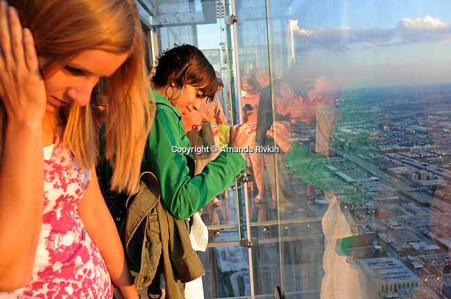 """Visitors look down from the newly opened glass balconies """"The Ledge"""" at the Skydeck at the Sears Tower in Chicago, Illinois on July 6, 2009."""