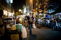 Jonathan Isaac Newman walks through the streets of Khao San after chanuka celebrations at Chabad Bangkok (Khao San), Thailand on 12th December 2009..Jon, an Irish/American, is a jeweller by profession, owns a video game manufacturing company in the USA, and used to work for the FBI. His brother is a rabbi. Jon has 4 children with his ex-wife, an Israeli. He speaks 7 languages and has recently decided to live to Bangkok. People often mistake Jon for a rabbi in Chabad Khao San because he wears a black coat and hat. However, soon after prayers, Jon changes into t-shirt and jeans, carrying his prayer clothes in a bag with him as he walks home..Photo by Suzanne Lee / For Chabad Lubavitch