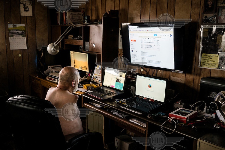 Les Baugh works on his computer setup at his home in Walden, Colorado.  Baugh lost both his arms at the shoulder in a freak electrical accident 40 years ago. Since then, he has managed life mostly without the help of prosthetic arms, which he finds to be more of an uncomfortable nuisance than a help. In 2013, Les underwent a state of the art surgery called Targeted Muscle Reinnervation, where the bundle of nerves at the stump of his shoulders were remapped to his pectoralis muscles. After he recovered from surgery, researchers at Johns Hopkins Applied Physics Lab fitted him with two robotic arms, called the MPL or Modular Prosthetic Limb, and he was able to manipulate objects with his hands, just by thinking about it. The MPL is a state of the art prototype, and not ready for take-home, so Baugh has been practicing mind control at home in rural Walden using a virtual reality game paired with less advanced prosthetic limbs. At a later stage the researchers at Johns Hopkins hope to get Les to try more advanced versions of the MPL  in the hope that his remapped nerves will have grown deeper into his pecs and he'll be able to manipulate the arms more effectively.