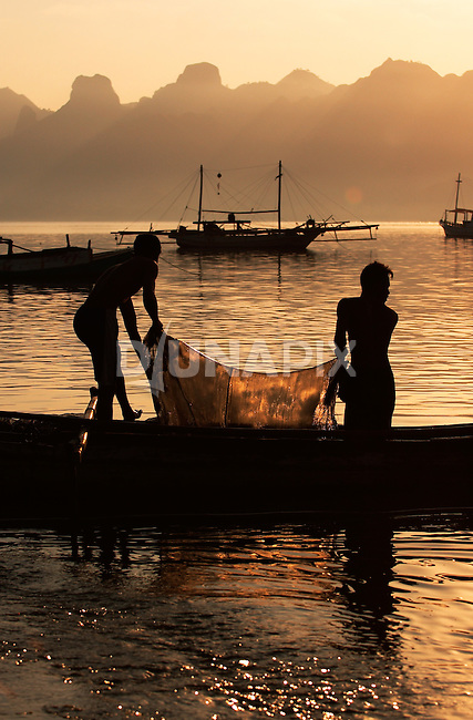 Silhouettes of fishermen at dawn, Komodo Village, Komodo National Park