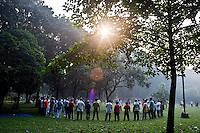Bangladeshi people perform morning exercise at a park in Dhaka, Bangladesh.