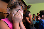A girl covers her face as she prays during the children's class of the United Methodist Church in the largely Roma neighborhood of Gorno Ezerovo, part of the Bulgarian city of Burgas. Residents here don't self-identify much as Roma, because of the negative connotations associated with the word, so many refer to themselves as a Turkish-speaking minority.