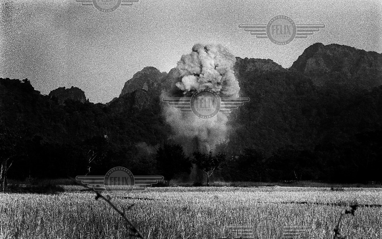 101 BLU 26 cluster bomblets are destroyed in a controlled explosion by a Mines Advisory Group (MAG) team which came to clear the area of unexploded ordnance (UXO)..Decades on, Laos is still living with the effects of the Vietnam war. Millions of bombs were dropped by US aircraft in Laos in an attempt to destroy the supply lines of North Vietnamese forces. Here in Bourlapha district, there were over 36,000 bombing missions. Many of the bombs remain deadly, with frequent accidents involving UXO.